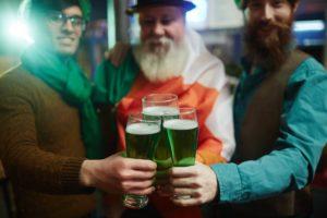 3 men holding green beer